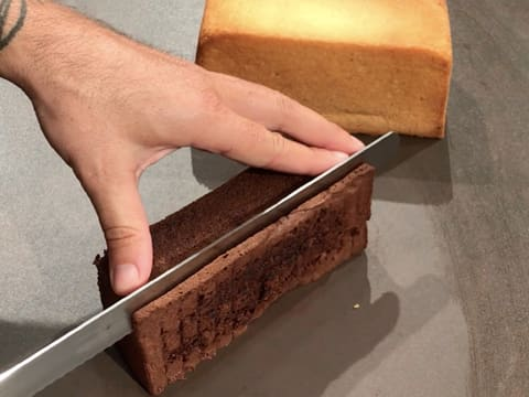 The chocolate sponge cake is trimmed with a serrated knife
