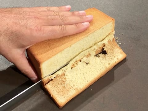 The vanilla sponge cake is trimmed with a serrated knife