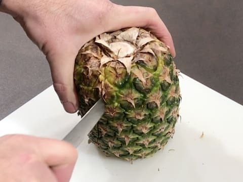 On a chopping board, cut a pineapple in half lengthwise with a knife
