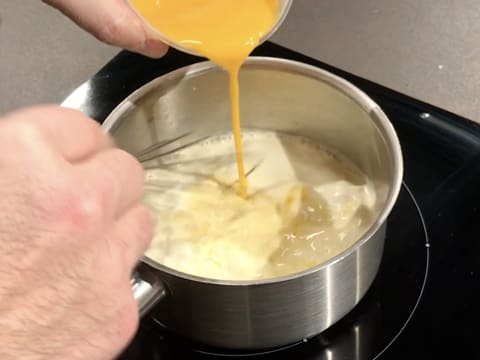 Add the egg yolks to the saucepan while whisking