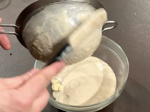 Scrape the bottom of the sieve with a spatula