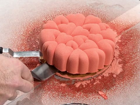Lift the pink cake with two metallic cranked spatulas
