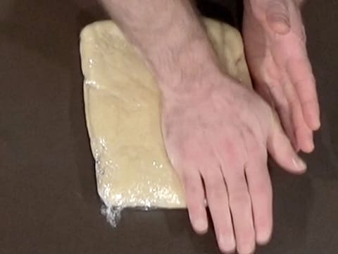 Flatten the dough wrapped in cling film