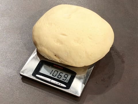 The brioche dough ball is on a kitchen scale