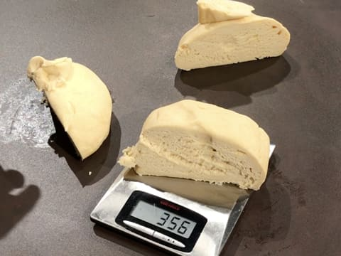 The brioche dough is divided in three equal balls, one dough ball is on the kitchen scale