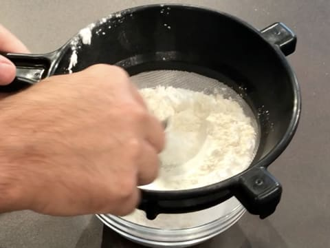 The flour and potato starch are sifted over a bowl